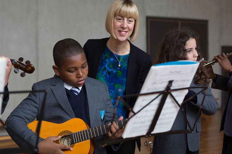 teacher with students playing guitar and flute